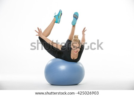 Gymnast girl in the sportswear lies on a blue fitball on the white background in the studio. She wears cyan-yellow sneakers, black pants and black t-shirt. She holds her stretched legs and arms in the