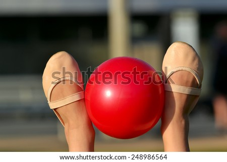 Gymnast's feet in toe shoes with red ball - stock photo