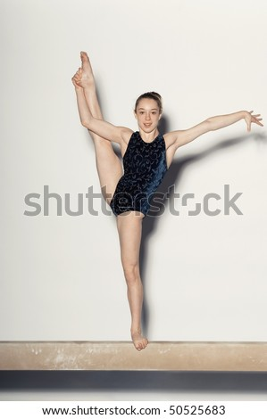 Gymnast (13-15) stretching one leg in air on balance beam, portrait - stock photo