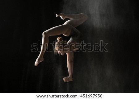 Gymnastic flexible woman handstand on equilibr at sprinkled flour - stock photo