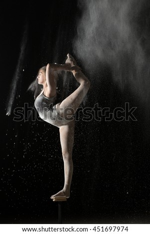 Gymnastic flexible woman standing on equilibr stand while sprinkled flour - stock photo