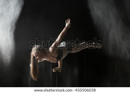 Gymnastic woman handstand on equilibr while sprinkled flour - stock photo
