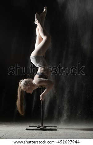 Gymnastic woman handstand on equilibre at sprinkled flour - stock photo