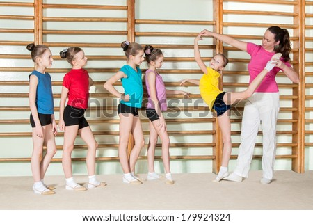 Gymnastics coach teaching little girls - stock photo
