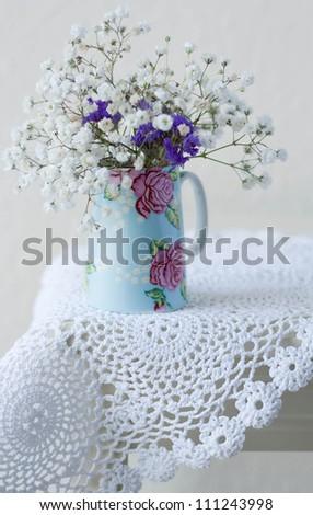 Gypsophila flowers in a small jug on a crochet doily - stock photo