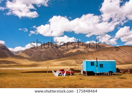 Gypsy caravan belongs the family of farmers lived in the mountains of Central Asia with beautiful white clouds above at the summer time. - stock photo
