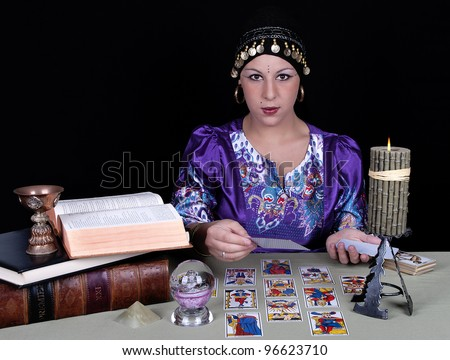 Gypsy fortune teller holding a tarot card - stock photo
