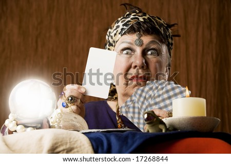 Gypsy fortune teller with crystal ball holding a blank tarot card - stock photo