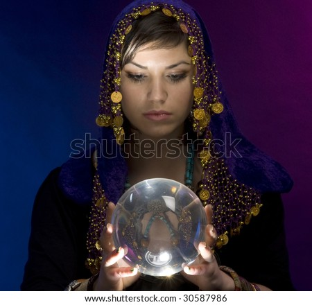 Gypsy fortuneteller uses a crystal ball to foretell the future - stock photo