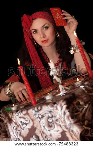 Gypsy woman sitting with cards. Isolated on black - stock photo