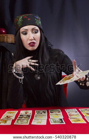 Gypsy woman wonders on the Tarot cards on a black background