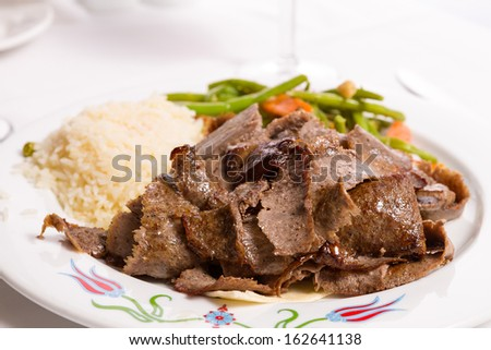 Gyro doner garnished with rice pilaf and vegetables served on thin lavash bread - stock photo