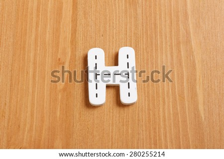 H, spell by woody puzzle letters with woody background - stock photo