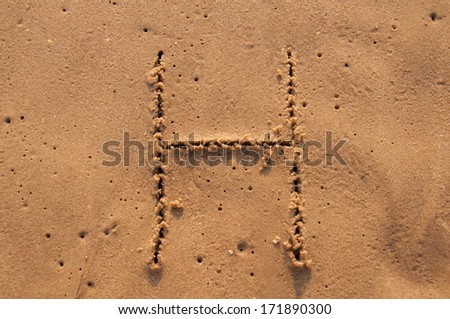 H text written in the sandy on the beach - stock photo