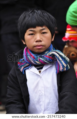 Ha Giang, Viet Nam - Feb 19, 2012: Unidentified traditionally dressed boy of Hmong ethnic minority tribe in Viet Nam. Hmong people are known for their indigo-dyed costumes and ornate silver jewellery. - stock photo