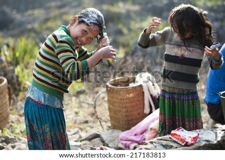 Ha Giang, Vietnam - Feb 16, 2013: Unidentified Hmong children washing their hair with family at a nature water well