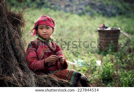 Ha Giang, VIETNAM - October 18, 2014: Portrait of an ethnic Hmong children in Ha Giang, Vietnam. Hmong children often do things on the field since childhood  - stock photo