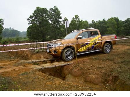 Ha Noi, Viet Nam - March 9, 2015: Nissan Navara NP300 2015 car crossing wood bridge on the test road in Vietnam - stock photo