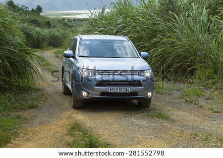 Ha Noi, Viet Nam - May 18, 2015: The Mitsubishi Outlander PHEV plug-in Hybrid CUV car  running on the dirt road in Vietnam - stock photo