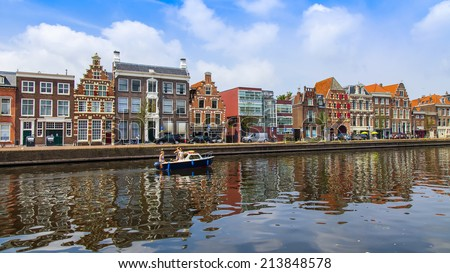Haarlem, Netherlands, on July 11, 2014. Typical urban view with old buildings on the bank of the channel. Reflection of houses in water