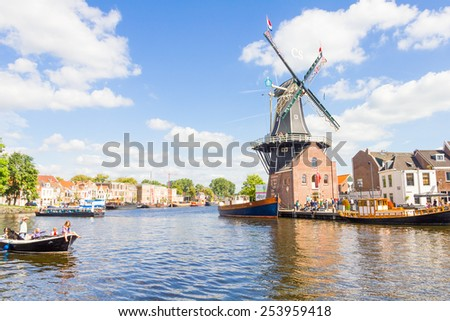 HAARLEM, THE NETHERLANDS - SEPTEMBER 1: Typical windmill and medieval architecture on September 1, 2012, Haarlem, Netherlands.The windmill, known as De Adriaan, is still working and is now a museum. - stock photo