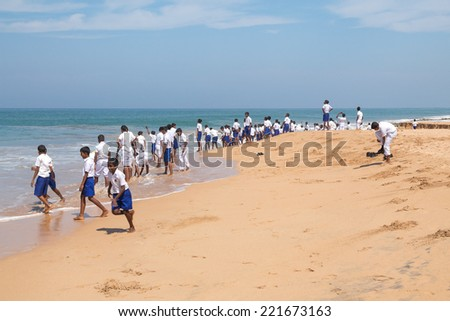 HABARADUWA, SRI LANKA - MARCH 11, 2014: Group of school kids at beach at Sea Turtle Farm and Hatchery. The center was started in 1986 and up to now they released more than 500,000 Turtles to ocean
