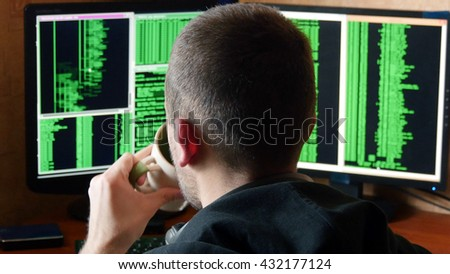 Hacker breaking code and drinking from the cup at your desk. Criminal hacker penetrating network system from his dark hacker room.  - stock photo