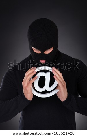 Hacker dressed in black wearing a balaclava with a white internet domain symbol in his hands as he stands in darkness conceptual of online safety and security and cyber crime - stock photo