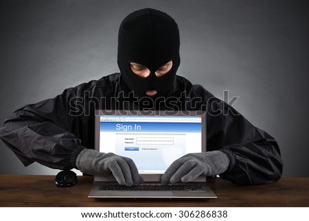 Hacker Hacking Account Of Social Networking Site On Laptop At Desk - stock photo
