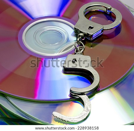 hacker handcuffs in CD conceptual workplace - stock photo