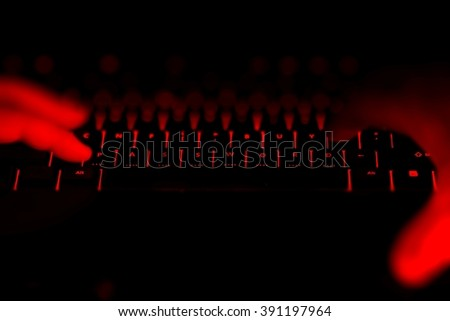 Hacker hands typing on the illuminated buttons of the keyboard by night. Internet safety concept.  - stock photo