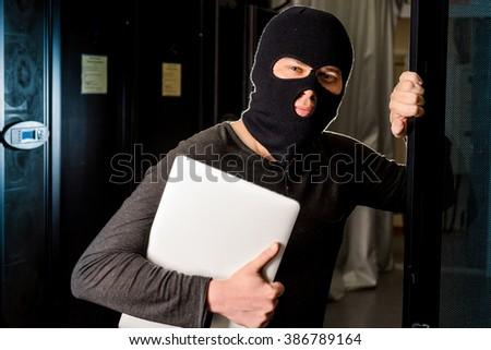 Hacker in a datacenter - stock photo