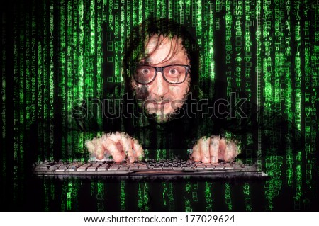 Hacker in Action on the keyboard  with matrix background - stock photo