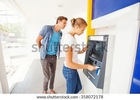 hacker in atm trying to steal pin code of woman's credit card - stock photo