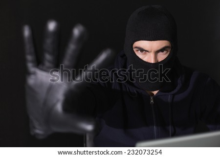 Hacker in balaclava gesturing and looking at camera on black background - stock photo