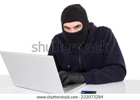 Hacker in balaclava hacking a laptop on white background - stock photo