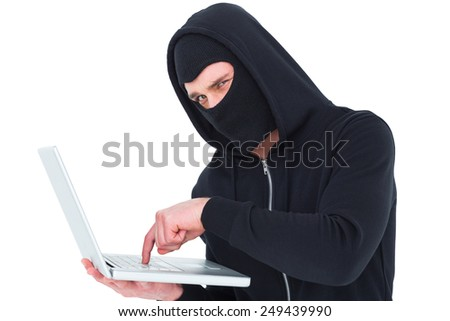 Hacker in balaclava typing on laptop on white background