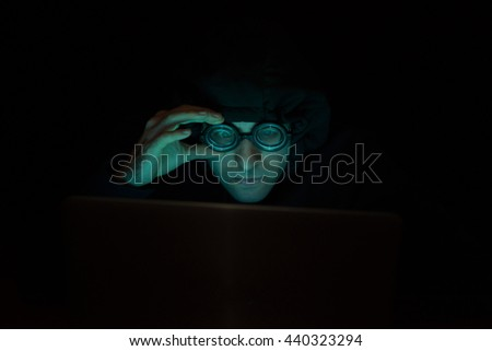 Hacker in front of his computer. Dark environment, monitor light
