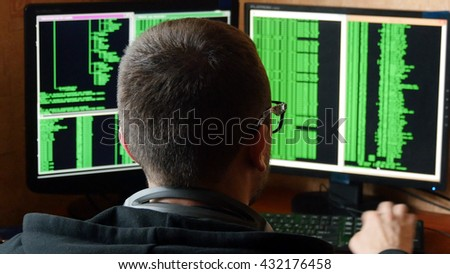 Hacker in glasses breaking code. Criminal hacker penetrating network system from his dark hacker room. Computer program writer at work in the office. Rear view. - stock photo