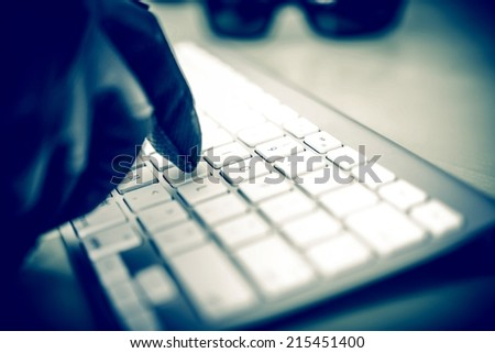 Hacker in Work. Hacker Hand in Black Glove Typing on the Keyboard. Closeup Photo Concept.  - stock photo