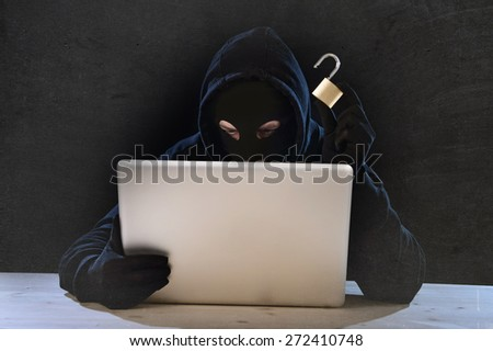 hacker man in black hood and mask with computer laptop holding lock in dangerous dark look hacking system having access to data info and privacy in business digital crack and cyber crime concept - stock photo