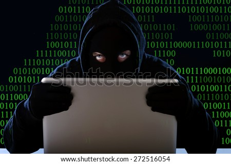 hacker man in black hood and mask with computer laptop in dangerous dark look hacking system having access to data info and privacy in business digital intruder and cyber crime concept - stock photo