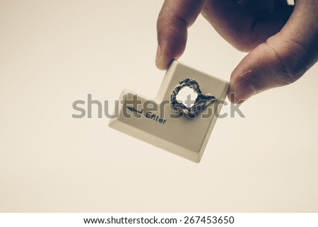Hacker's hand picking up computer enter button with a hole representing computer security breach - stock photo