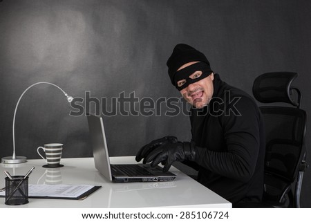 Hacker stealing data  from a laptop and laughing  - stock photo