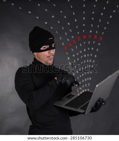 Hacker stealing data from a laptop on black background - stock photo