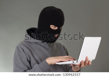 hacker stealing data from white notebook
