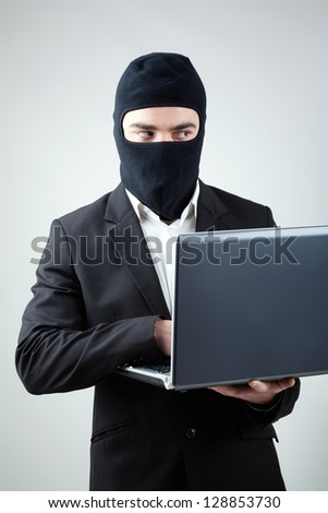Hacker stealing information from laptop - stock photo