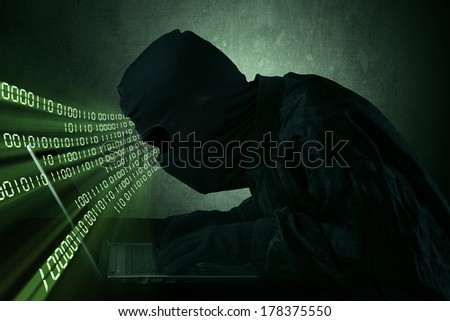 Hacker typing on a laptop with binary code in front of a computer screen - stock photo