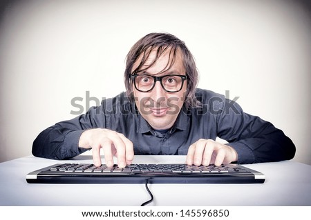 Hacker typing on the keyboard and mocking - stock photo