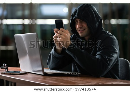 Hacker using a smartphone - stock photo